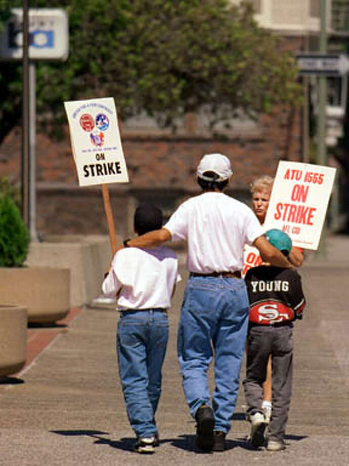 Ray Lowe holds his two sons, Brian Lowe, 9, left, and Brennen Lowe, 7, while talking with Dolores Ramirez on San Leandro as they picket in front of the BART offices on Oak Street in Oakland on Sunday, September 7, 1997. The first day of the strike for BART employees was a quiet day as negotiations continued before crunch time on Monday when the weekday commuters would feel the impact of the strike. (CHRONICLE PHOTO BY CARLOS AVILA GONZALEZ) Photo: CARLOS AVILA GONZALEZ