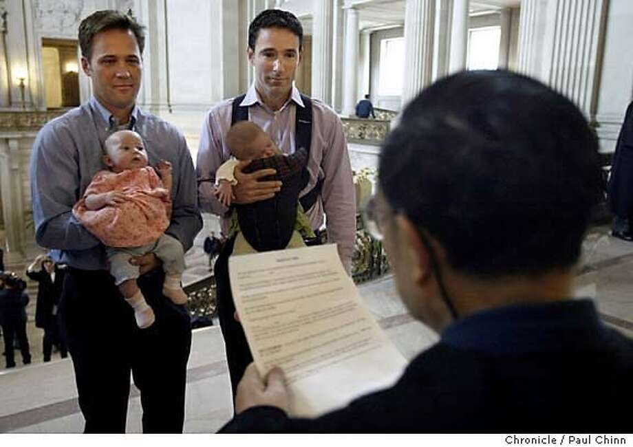 "** ADVANCE FOR SUNDAY, FEB. 29 ** Eric Ethington, left, exchanges marriage vows with Doug Okun, while holding their twin daughters, Sophia Rose and Elizabeth Ruby, in front of marriage commissioner Richard Ow at San Francisco's City Hall, Feb. 13, 2004. Before a civil servant pronounced them ""spouses for life"" Ethington, 37, and Okun, 38, already considered themselves married, as the two men had been together eight years and had recently become fathers. (AP Photo/San Francisco Chronicle, Paul Chinn) Photo: PAUL CHINN"
