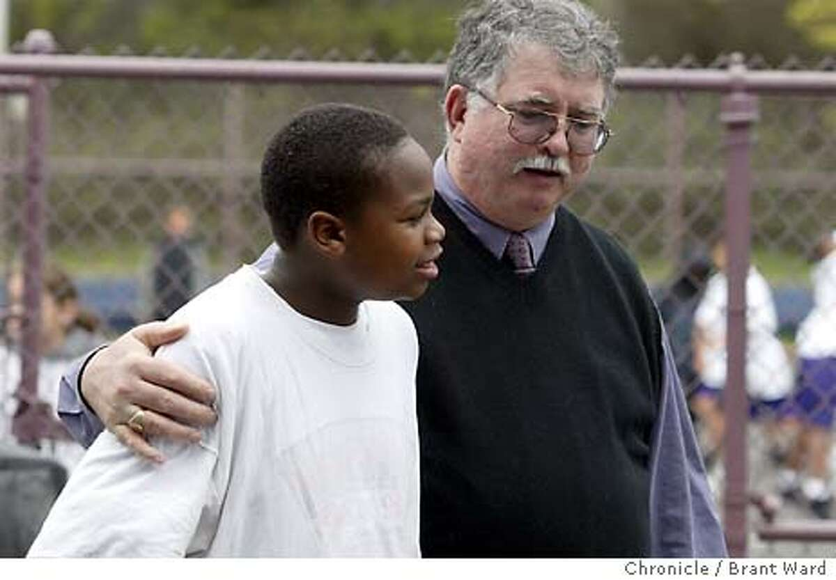 """grief_194_bw.jpg Principal Jim Dierke walks with student Tauvares Wooten during lunchtime...Principal Jim Dierke is trying to find the money to hire a """"grief"""" counselor at his Visitacion Valley Middle School in San Francisco after the numerous killings in the area have affected his students. BRANT WARD / The Chronicle"""