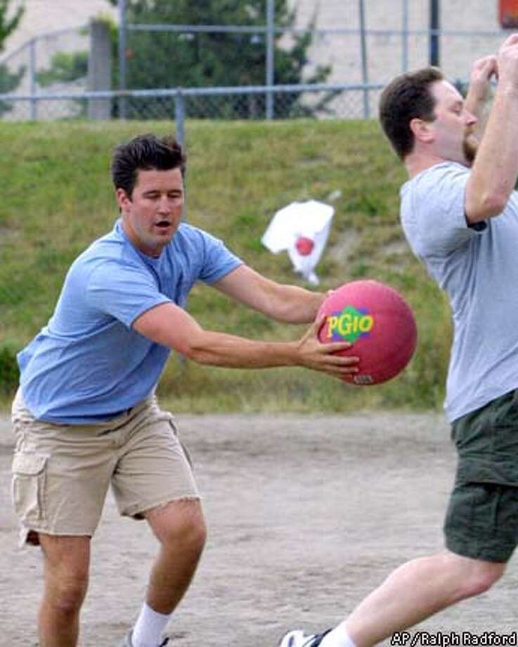 ** ADVANCE FOR WEEKEND, AUG. 10, 11 ** Matt Bratlien, from Seattle, tags George Dart, right, out along the baseline during a game of kickball in Seattle, July 2, 2002. Adults are going back to simpler times in games that have no technical requirements. Wiffle ball, kickball, dodgeball, even jump rope, are becoming increasingly popular with adults. (AP Photo/Ralph Radford) Photo: RALPH RADFORD
