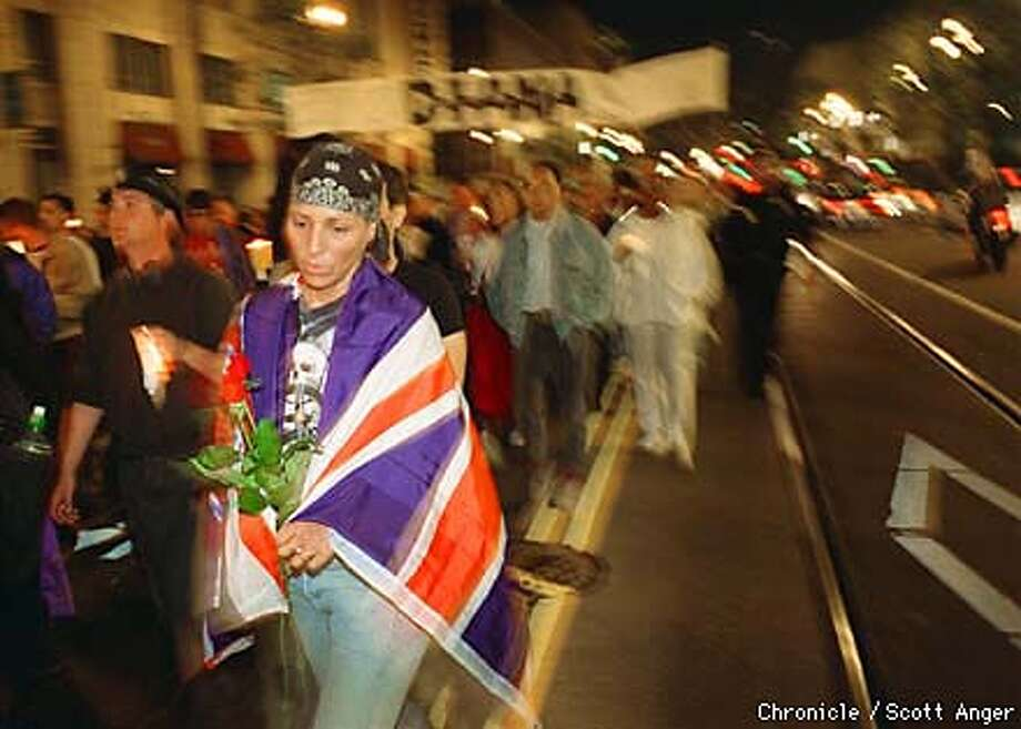 A marcher wrapped in the British flag walks along Market Street Friday night with an estimated 5,000 others as part of a candle light memorial for the late Princess Diana. (Scott Anger/the Chronicle) Photo: Scott Anger
