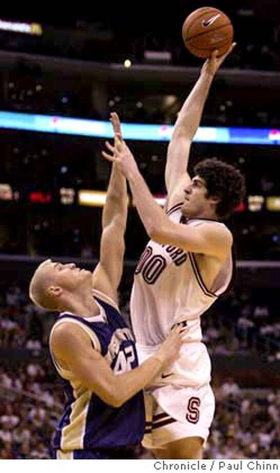 Joe Kirchofer towers over Washington's Mike Jensen as he goes up for two points in the second half. The Stanford Cardinal vs. the Washington Huskies in the Pac-10 basketball tournament championship game on 3/13/04 in Los Angeles. PAUL CHINN/The Chronicle Photo: PAUL CHINN