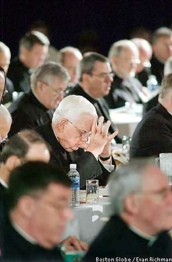 (NYT2) DALLAS -- June 14, 2002 -- Faced with a public outcry over sexual molesters within the church, the nation's Roman Catholic bishops meeting in Dallas appeared ready on Friday to approve a policy that would remove all offenders from parish life and order most guilty priests defrocked. Cardinal Bernard Law of Boston, center, in prayer along with fellow church leaders during a morning session of the United States Conference of Catholic Bishops, Friday in Dallas. (Evan Richman/The Boston Globe) Photo: EVAN RICHMAN
