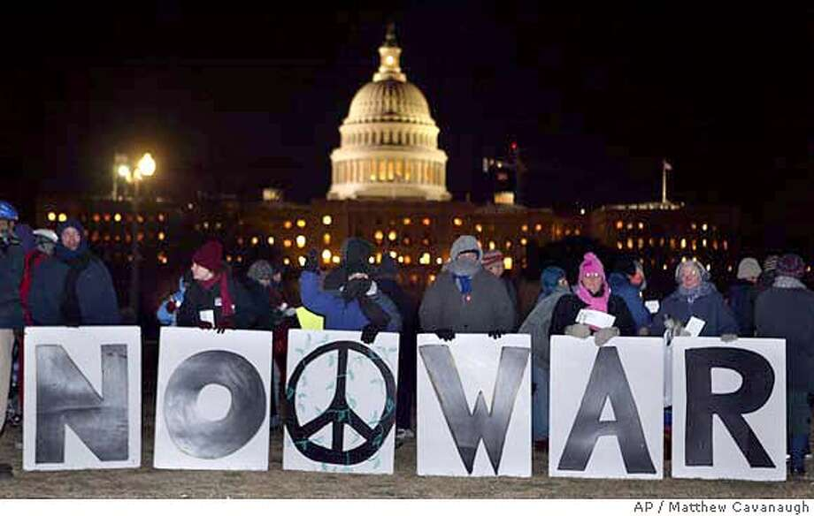 Anti war protesters hold signs outside the Capitol during the President's State of The Union address on Tuesday, Jan. 20, 2004. (AP Photo/Matthew Cavanaugh) Photo: MATTHEW CAVANAUGH