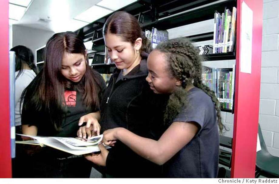 "SHOWN: In the stacks of the new library, L to R: Cynthia Aguilar, 11, Anna Quintero, 11, and Trevlyn Mitchell, 12, all read ""Birds From Forest to Family Room."" We visit the brand new library at Richmond's (CA) brand new Lavonya DeJean Middle School, which stands to be closed due to $16.5 in cuts approved by the West County School Board this week. Writer is Simone Sebastian. Katy Raddatz / The Chronicle Photo: Katy Raddatz"