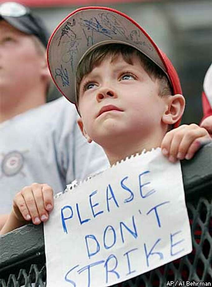 Tristan Lana, 6, expresses his feelings towards a possible players strike during batting practice, Friday, Aug. 16, 2002, prior to a game between the Houston Astros and Cincinnati Reds in Cincinnati. Earlier in the day, the baseball players union set a strike deadline of Aug. 30, moving the sport closer to its ninth work stoppage since 1972. (AP Photo/Al Behrman) Photo: AL BEHRMAN