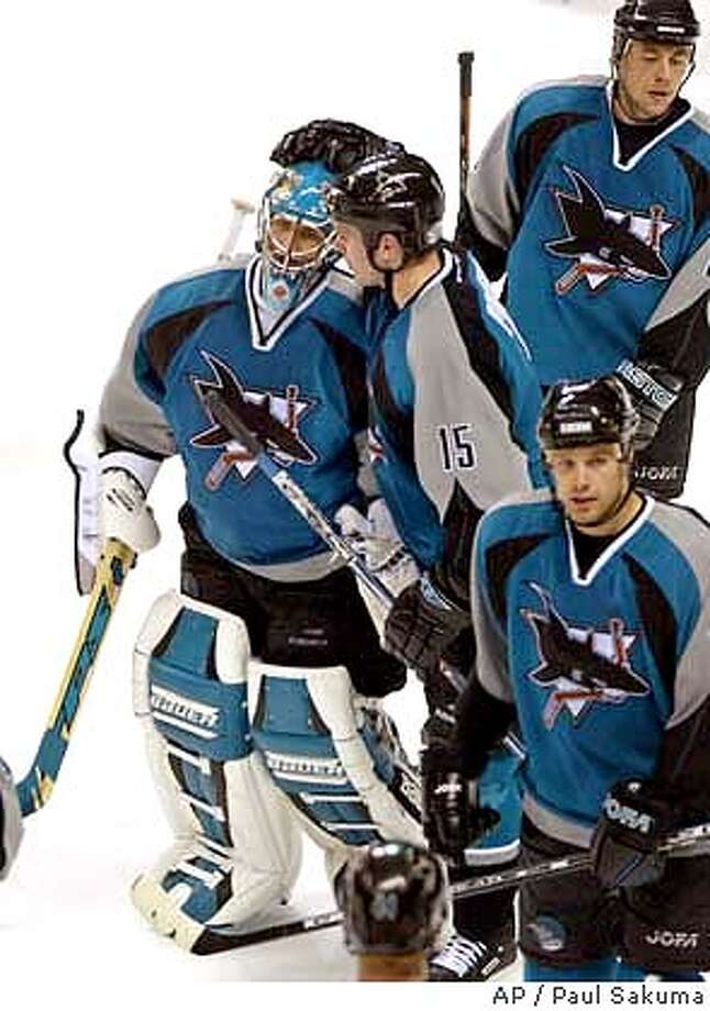 ** ADVANCE FOR WEEKEND EDITIONS JAN. 17-18 ** San Jose Sharks goalie Evgeni Nabokov, left, is hugged by center Wayne Primeau after their game against the Dallas Stars, Tuesday, Jan. 13, 2004 in San Jose, Calif. To the amazement of even their coach, the Sharks are one of the NHL's biggest surprise. They have surged to a healthy lead in the Pacific Division despite a star-free roster, a middling offense and a top-to-bottom franchise upheaval in the past 13 months. (AP Photo/Paul Sakuma) **ADVANCE FOR WEEKEND EDITIONS JAN. 17-18 Photo: PAUL SAKUMA