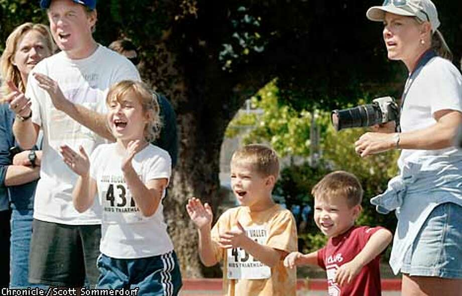 From left to right: Mark Hazelwood, Jackie Hazelwood (#437), Carson Kelley (#451), ...the littlest boy is unidentified....., and finally Molly Kelley (far right) yell encouragement to Cameron Kelley as he rides by on his second lap in the bike portion of the race. The Hazelwoods are from San Francisco, and the Kelleys are from Portola Valley) (SF CHRONICLE PHOTO BY SCOTT SOMMERDORF) Photo: SCOTT SOMMERDORF