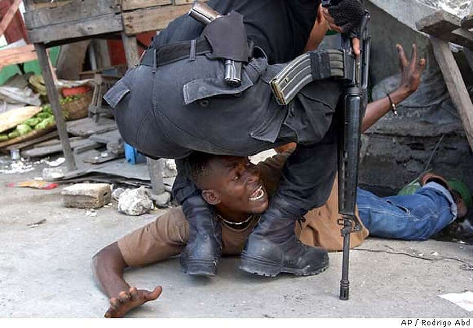 A policeman detains a man that was allegedly throwing stones at anti-Aristide demonstrators in Port-au-Prince, Sunday, Jan 18, 2004. About 4000 anti Aristide protesters marched today demanding the resignation of Haiti's President. (AP Photo/Rodrigo Abd) Photo: RODRIGO ABD