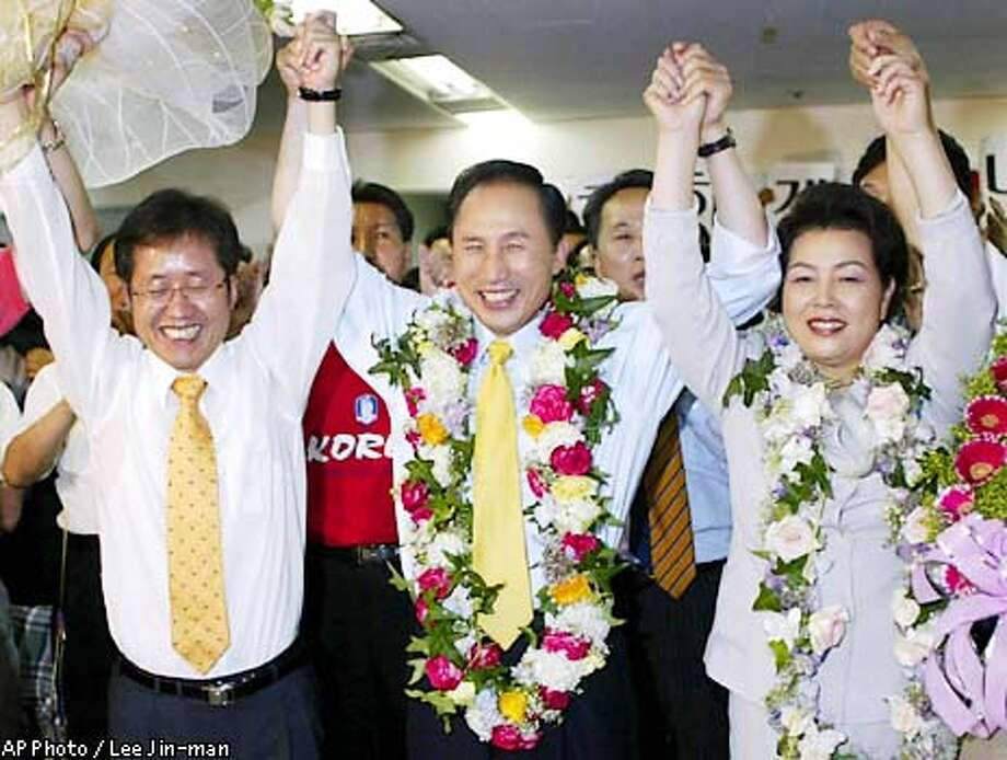 Lee Myung-bak, center, the main opposition Grand National Party candidate for Seoul mayor, celebrates his lead in the polls with his wife Kim Yoon-ock, right, and Hong Jun-pyo, a lawmaker of the Grand National Party, at the his office in Seoul, Thursday, June 13, 2002. South Korea's main opposition party led in early returns Thursday in local elections that were widely seen as a bellwether for presidential voting in December. (AP Photo/Lee Jin-man). Photo: LEE JIN-MAN