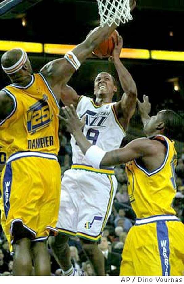 Golden State Warriors' Erick Dampier tries to block Utah Jazz guard Raja Bell during the first half Monday, Jan. 19, 2004, in Oakland, Calif. Mickael Pietrus of France is on the right. (AP Photo/Dino Vournas) Photo: DINO VOURNAS