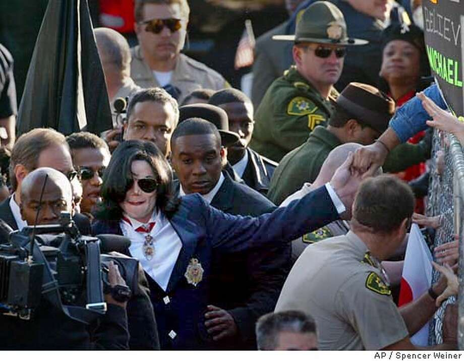 Michael Jackson reaches out to a fan as he arrives at the Santa Maria, Calif., courthouse Friday morning, Jan. 16, 2004, for his arraignment on child molestation charges. Jackson is charged with seven counts of performing lewd or lascivious acts on a child under 14 and two counts of administering an intoxicating agent (AP Photo/Spencer Weiner, pool) Michael Jackson reaches out to a fan as he arrives at the Santa Maria courthouse Friday morning for his arraignment on child molestation charges. Photo: SPENCER WEINER