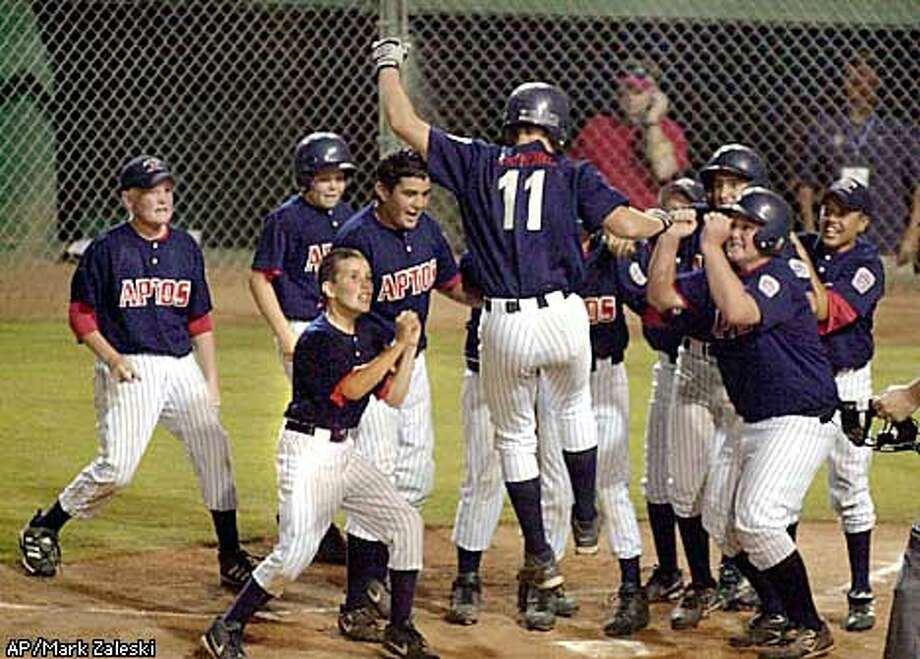 Aptos' Tyler Raymond (11) celebrates with teammates as he steps on home plate after hitting a three-run home run in the sixth inning to defeat Glendale, Ariz., 4-3 in the Little League Western regional championship game Tuesday, Aug. 12, 2002, in San Bernadino, Calif. (AP Photo/The Press Enterprise, Mark Zaleski) Photo: MARK ZELESKI