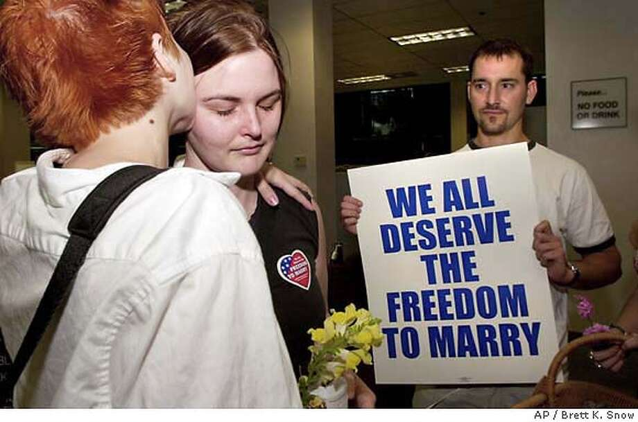 Shannon O'Leary, 23, center, is comforted by Crystal Richards, 22, left, of Riverside, Calif., after being denied a marriage license at the San Bernardino County Hall of Records in San Bernardino, Calif., Wednesday, March 10, 2004. The couple were supported by L.J. Carusone, holding sign, theexecutive director of Marriage Equality California. (AP Photo/San Bernardino Sun, Brett K. Snow) MANDATORY CREDIT MAGS OUT Photo: BRETT K. SNOW