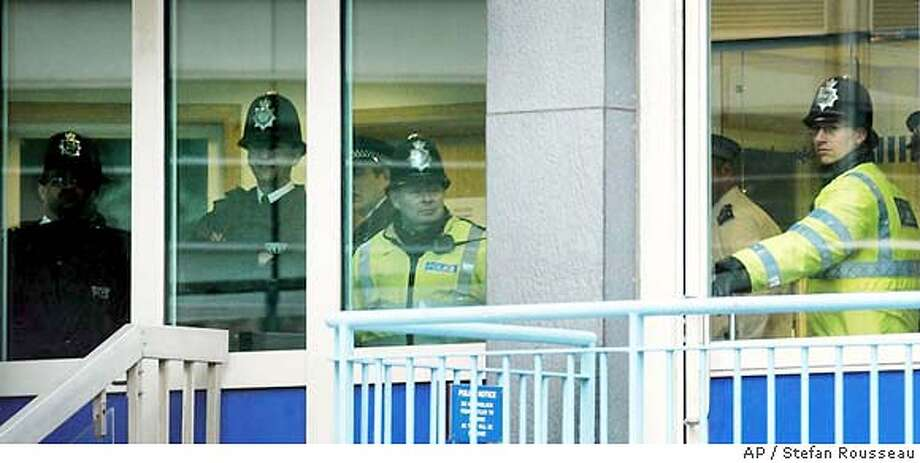 Police keep an eye on the media at Paddington Green Police Station in London, Wednesday March 10, 2004, as four of the five Britons released from Guantanamo Bay were being held there for further questioning. They were arrested under Britain's Terrorism Act 2000 after arriving Tuesday. The fifth was released after being questioned briefly. (AP Photo/Stefan Rousseau/PA) ** UNITED KINGDOM OUT MAGAZINES OUT ** UNITED KINGDOM OUT MAGAZINES OUT Photo: STEFAN ROUSSEAU