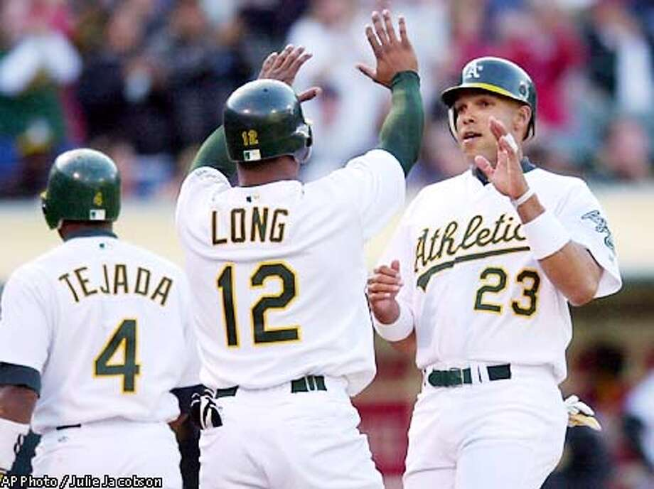 Oakland Athletics' David Justice, right, is greeted at home plate by Terrence Long, center, as Miguel Tejada, left, heads for the dugout after the three scored on a double hit by Jermaine Dye against the Milwaukee Brewers during the first inning Tuesday, June 11, 2002 in Oakland, Calif. (AP Photo/Julie Jacobson) Photo: JULIE JACOBSON