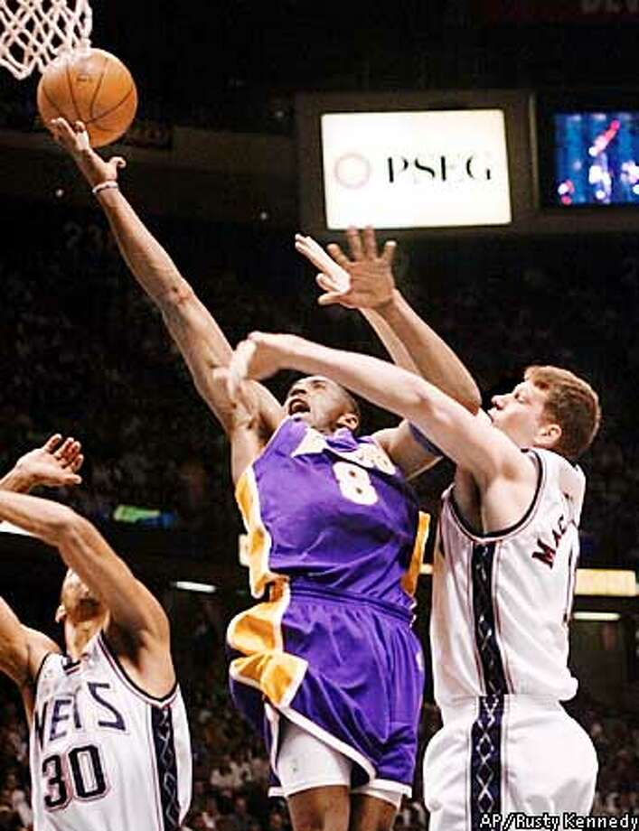 Los Angeles Lakers' Kobe Bryant (8) goes to the basket against New Jersey Nets' Todd MacCulloch, right, and Kerry Kittles, left, in the first half of Game 3 of the in East Rutherford, N.J. Sunday June 9, 2002. (AP Photo/Rusty Kennedy) Photo: RUSTY KENNEDY