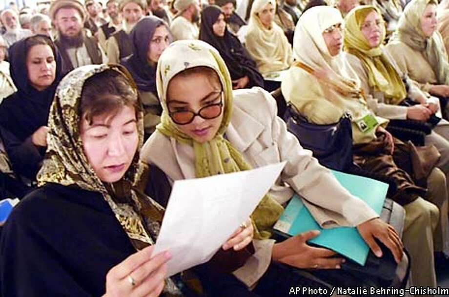 "Women delegates read an official statement together during the opening session of the Loya Jirga, in Kabul, Tuesday, June 11, 2002. More than 1500 delegates from through out the country will meet this week at the Loya Jirga, or ""Grand Council"" to select new leadership for Afghanistan. ( AP Photo/Natalie Behring-Chisholm/Pool) Photo: NATALIE BEHRING-CHISOLM"