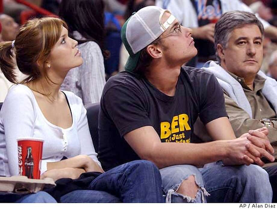 Tennis player Andy Roddick, right, and actress-singer Mandy Moore, left, watch a replay in the game between the the New York Knicks and the Miami Heat Saturday, Dec. 27, 2003 in Miami. The person on the right is unidentified. (AP Photo/Alan Diaz) Photo: ALAN DIAZ