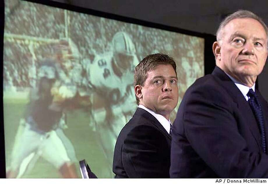 Former Dallas Cowboy quarterback Troy Aikman, left, and Cowboys team owner Jerry Jones watch highlights from Aikman's career with the team during a news conference in Irving, Texas, announcing his retirment from the NFL, Monday, April 9, 2001. Aikman was waived by the Cowboys on March 7, a day before he was due a $ 7 million bonus and seven-year contract extension. (AP Photo/Donna McWilliam) CAT Photo: DONNA MCWILLIAM