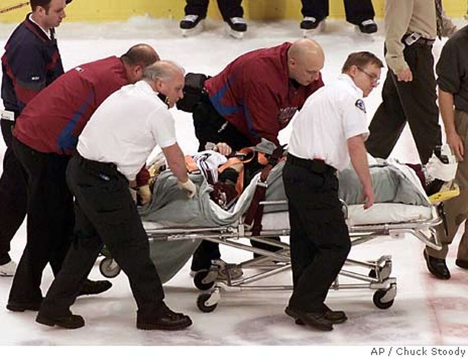 Colorado Avalanche Steve Moore is taken off the ice by medical staff on a strecher after he was hit by Vancouver Canucks Todd Bertuzzi during the third period of NHL action in Vancouver, British Columbia, Monday, March 8, 2004. Moore was taken from the ice on a stretcher after being pummelled to the ice from behind by the Vancouver Canucks' Todd Bertuzzi during the third period of the game. (AP Photo/Chuck Stoody) Medical personnel take Steve Moore off the ice in a stretcher Monday night after he was laid low by Vancouver's Todd Bertuzzi. Photo: CHUCK STOODY
