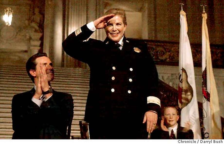 New fire chief, Joanne Hayes-White salutes the crowd after being sworn in by mayor Gavin Newsom, bottom left, at City Hall. 1/16/04 in San Francisco. DARRYL BUSH / The Chronicle Photo: DARRYL BUSH
