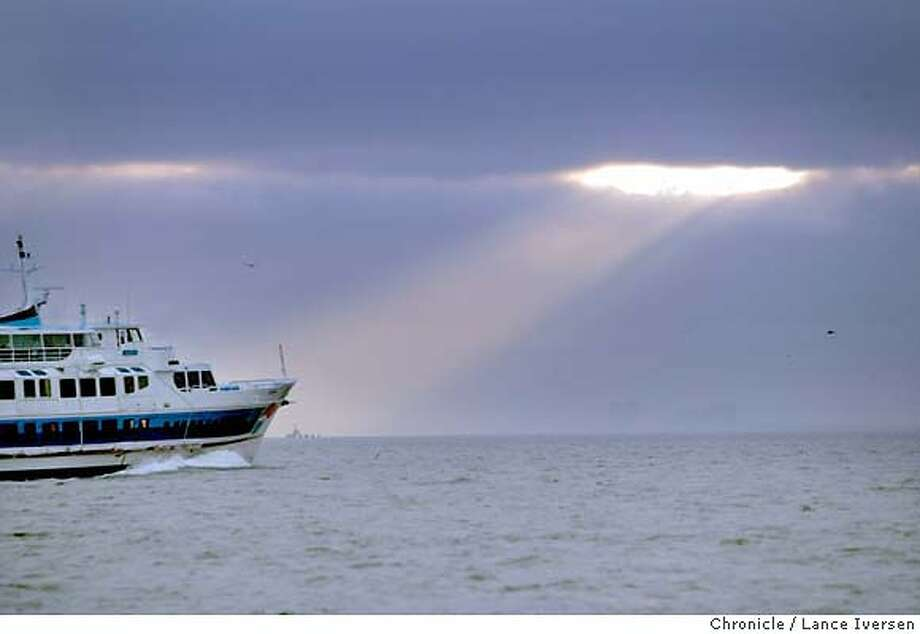 FEATURE011604_LI.jpg  Commuters aboard the Larkspur ferry, Marin witnessed sunrise as a shaft of light momentarily broke through the over cast off angel Island friday. By Lance Iversen/SAN FRANCISCO CHRONICLE MANDATORY CREDIT FOR PHOTOG AND SF CHRONICLE/ -MAGS OUT-WIRE SERVICES OUT Gary Fong 415-777-8428 Photo: Lance Iversen
