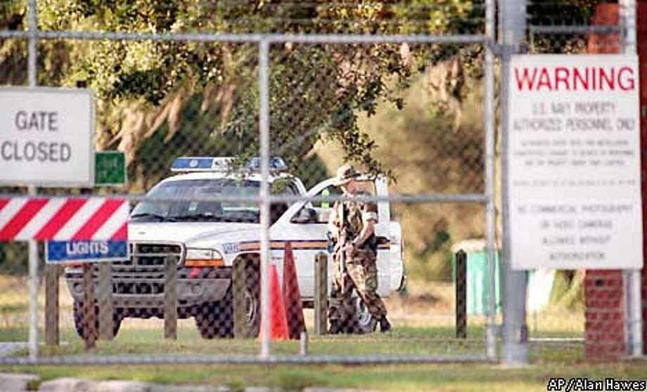 """A military policeman stands guard at a North Charleston, S.C., gate of the Charleston Naval Weapons Station on Monday, June 10, 2002. Jose Padilla, also known as Abdullah al Muhajir, who is accused of plotting with al-Qaida terrorists to detonate a """"dirty bomb"""" to spread radioactive material, is being held at the Navy brig on the facility. (AP Photo/The Post and Courier, Alan Hawes) Photo: ALAN HAWES"""