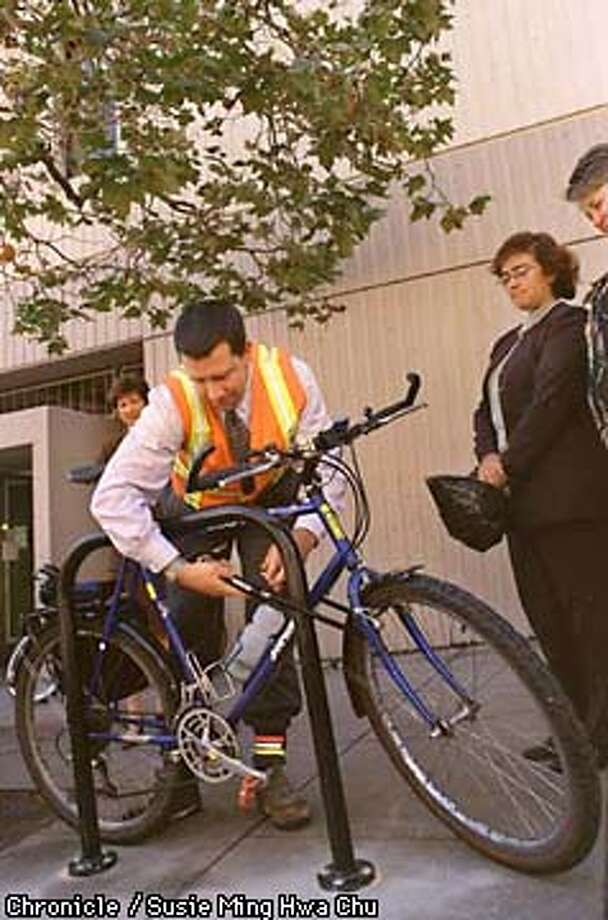 BIKERACK/C/21AUG97/MN/SMHC  Adam H. Gubser, Assistant Bicycle Program Manager at DPT, locks his bike at the unveiling of the city's first bike rack on a public sidewalk outside the Air Quality Management District building on Ellis. CHRONICLE PHOTO BY SUSIE MING HWA CHU.