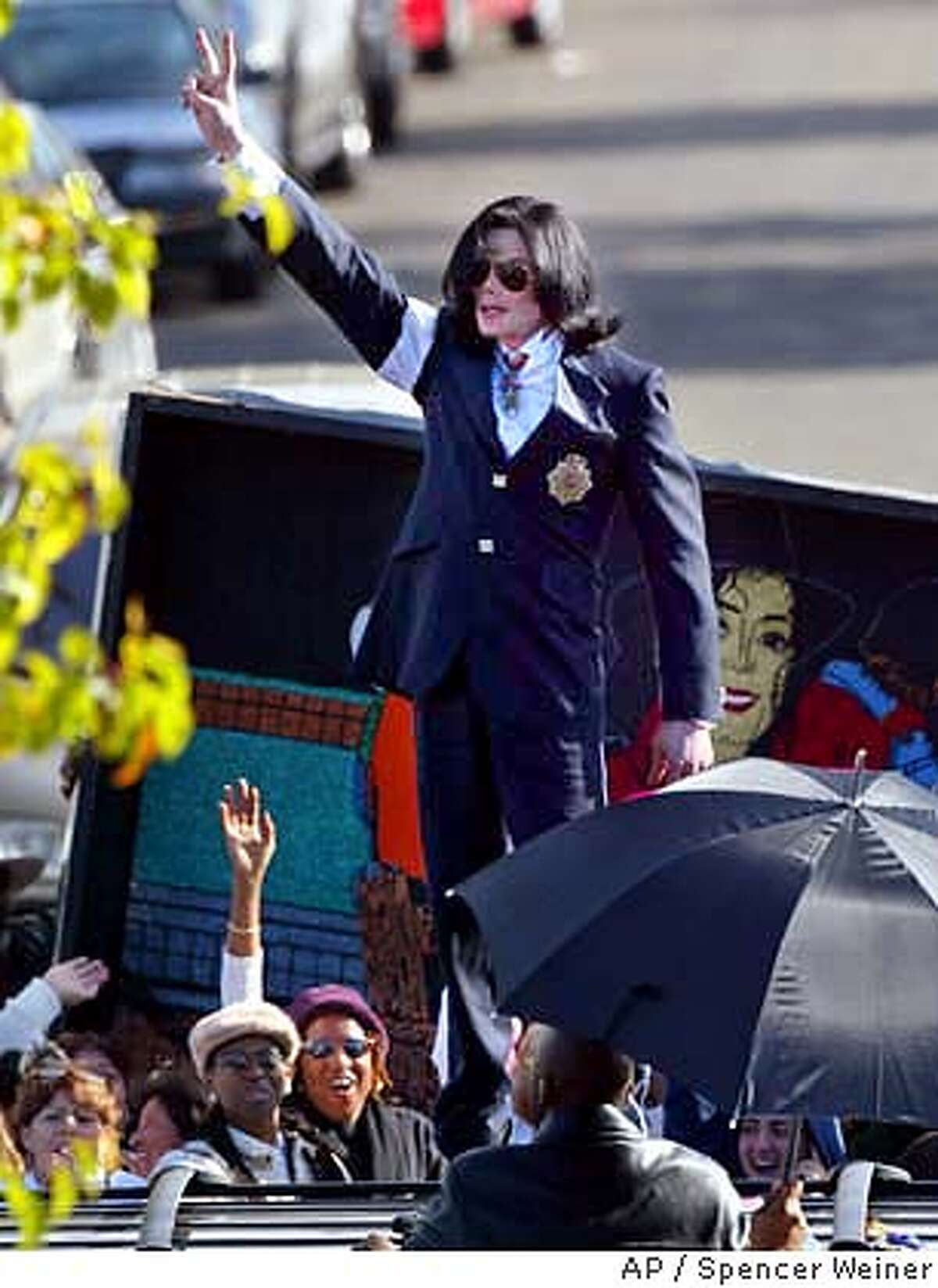 flashes the peace sign to his fans from on top of his limousine as he leaves the courthouse in Santa Maria, Calif., after his arraignment on child molestation charges Friday, Jan. 16, 2004. (AP Photo/Spencer Weiner, pool)