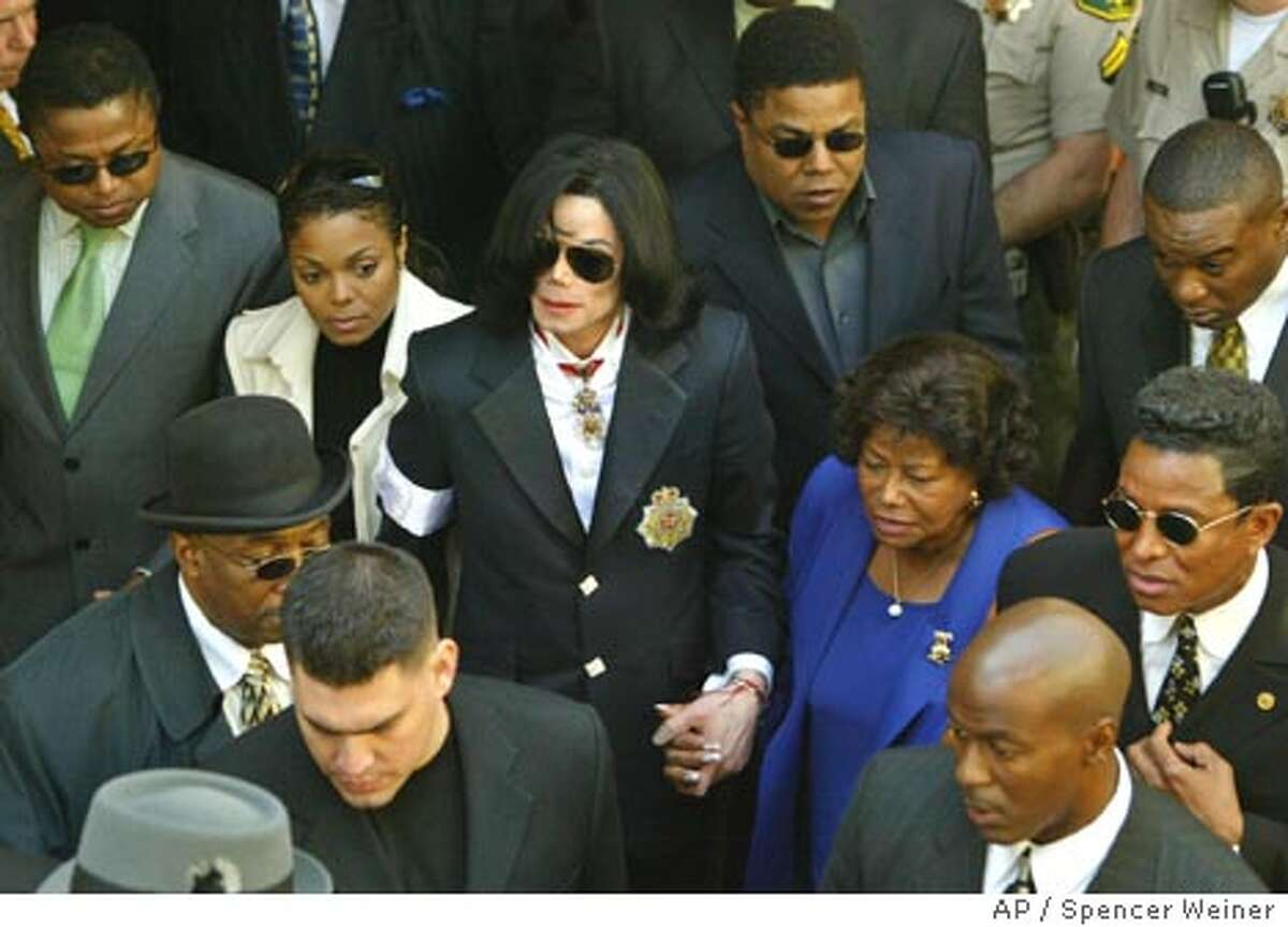 Michael Jackson exits the courthouse in Santa, Maria, Calif., holding hands with his family including, his sister Janet, his mother Katherine and brother Jermaine, right, Friday, Jan. 16, 2004, after his arraignment on child molestation charges. (AP Photo/Spencer Weiner, pool)