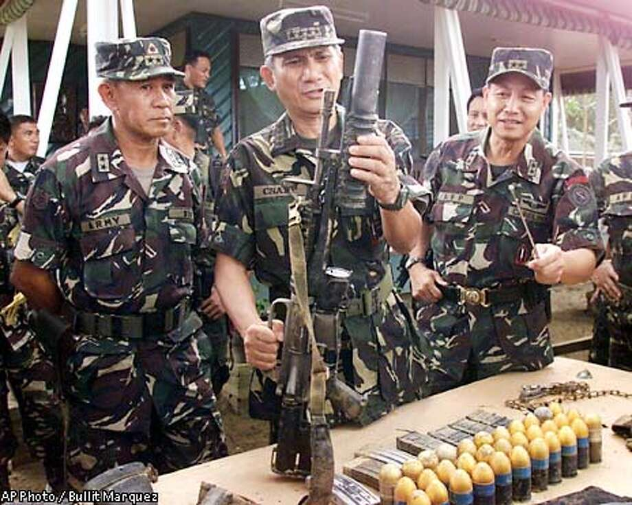 New Armed Forces Chief Gen. Roy Cimatu, center, cocks an M-203 rifle as he presents weapons to the media, Saturday, June 8, 2002, in the remote town of Sirawai, southern Philippines and other items recovered by Philippine troopers in their encounter with Muslim Abu Sayyaf kidnappers which rescued two hostages but killed two others Friday. At left is Maj. Gen. Glicerio Sua, head of the task force to rescue the hostages and Maj. Gen. Ernesto Carolina, right, chief of the Southern Command. (AP Photo/Bullit Marquez) Photo: BULLIT MARQUEZ