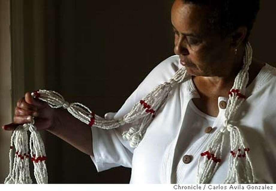 "Paris Williams, of Oakland, Ca., wears a ""Mazo,"" a set of beadwork which is part of the worship if Orishas. Mazos are one of the most complex types of beadwork. A mazo consists of various strings of beads that are divided into sections called casetas (huts), separated by larger beads called glorias. A number of tassel-like strands called mo�as hang from the front and sides of the necklace. The arrangement of beads is determined by the ritual number associated with the orisha for whom the mazo is intended. Several items that are commonly found in the worship of Orishas, or deities that come from West African tradition. Story is about botanicas, spiritual supply stores for candles, potions, incense and other items used in the worship of the ""orishas,"" the gods of santeria and related Western African religions. Photo taken on 03/04/04 in Berkeley, Ca. Photo By Carlos Avila Gonzalez / The San Francisco Chronicle Photo: Carlos Avila Gonzalez"
