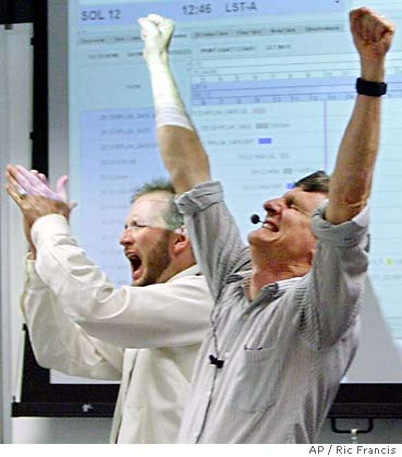 Steve Squyres, right, principal investigator for Mars Exploration Rover, and Mark Boyles, assurance manager, celebrate Thursday, Jan. 15, 2004, at NASA's Jet Propulsion Laboratory, in Pasadena, Calif., after receiving confirmation that the maneuver to get the Spirit rover off its lander was a success. It rolled onto Mars early Thursday, placing its six wheels on martian ground for the first time since it bounced down on the red planet nearly two weeks ago. (AP Photo/  Ric Francis Photo: RIC FRANCIS