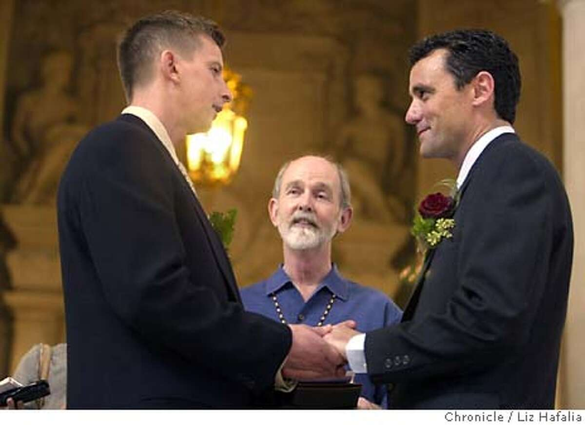 """David Knight, right, the estranged son of state Sen. William """"Pete"""" Knight, who authored California's law banning same-sex marriage, holds hands with his long-time partner, Joe Lazzaro, left, as they take their wedding vows, Tuesday, March 9, 2004, at City Hall in San Francisco. Performing the service is Donald Bird, center. (AP Photo/The San Francisco Chronicle, Liz Hafalia)"""