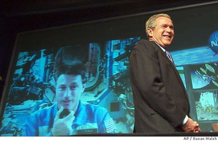 President Bush is all smiles as he talks with NASA astronaut Commander Michael Foale, of Cambridge, England, working aboard the international space station, at the start of a news conference at NASA Headquarters in Washington, Wednesday, Jan. 14, 2004. Bush proposed on Wednesday to develop a new spacecraft to carry Americans back to the moon by 2015, and to establish a long-term base there as an eventual springboard to Mars and beyond. (AP Photo/Susan Walsh) Photo: SUSAN WALSH