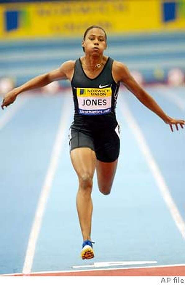 Marion Jones of the United States, crosses the finish line in second place in the women's 60-meter sprint at Birminghams Indoor Arena in England, Friday Feb. 20, 2004, during the Norwich Union Grand Prix indoor athletics met . Belguim's Kim Gevaert finished in first. (AP Photo/Dave Caulkin) Photo: DAVE CAULKIN