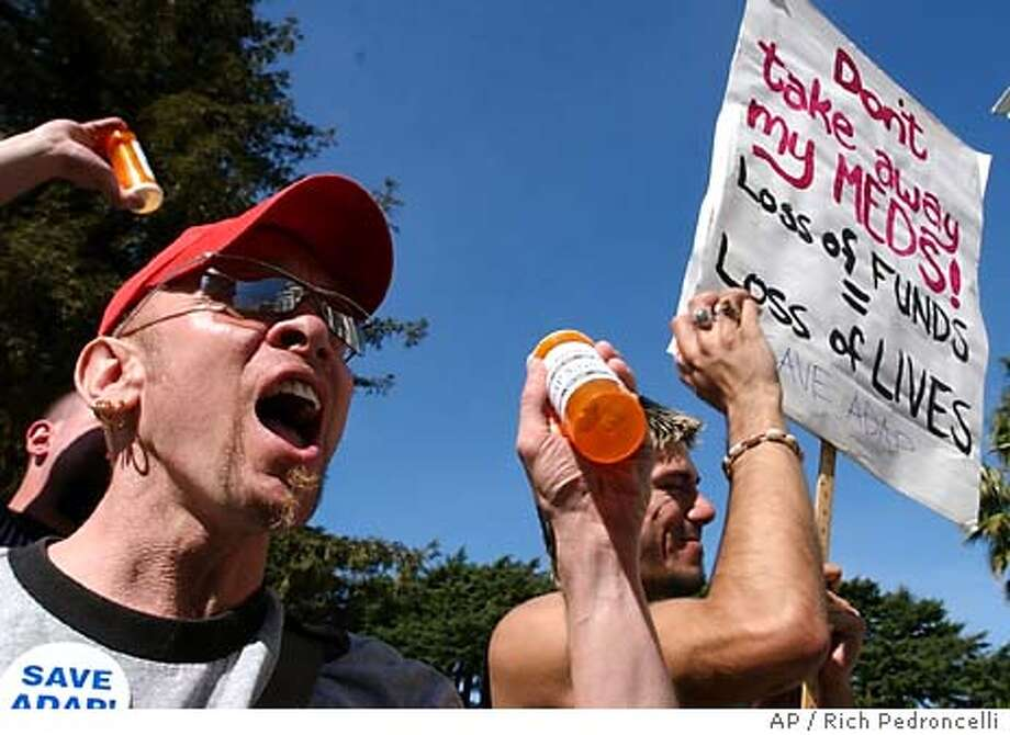 Lee Jewell, left, and Kai Noble, right, both of San Franciso shake pill bottles as they demonstrate against Gov. Arnold Schwarzenegger's plans to cap a number of public health programs during a rally held in Sacramento, Calif., Monday, March 8, 2004. More than 200 people demonstrated against Schwarzenegger's budget proposal which would cap spending on the AIDS Drug Assistance Program at current levels and maintain sevices only for existing clients while placing a cap on accepting any future clients. (AP Photo/Rich Pedroncelli) Photo caption Photo: RICH PEDRONCELLI