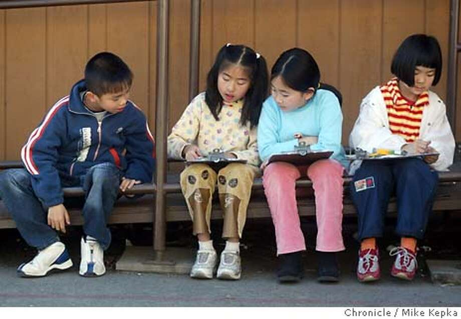 oakapi100028_mk.jpg Licoln second grader, Jason Fan, 7, watches as his classmates Emily Liu, 8, Kelly Tan, 8, and Cindy Ng, 7 finish their unfinished class work during recess.  Lincoln Elementary in Oakland's Chinatown blasted out of the gate five years ago when state testing began, and has remained a high-scoring elementary school ever since. Ninety percent of its children are sons and daughters of Chinese immigrants, and most meet poverty guidelines for free lunch. Half are learning English.  Mike Kepka / The Chronicle Lincoln Elementary second-graders Jason Fan, Emily Liu, Kelly Tan and Cindy Ng talk about class work during recess. Photo: Mike Kepka