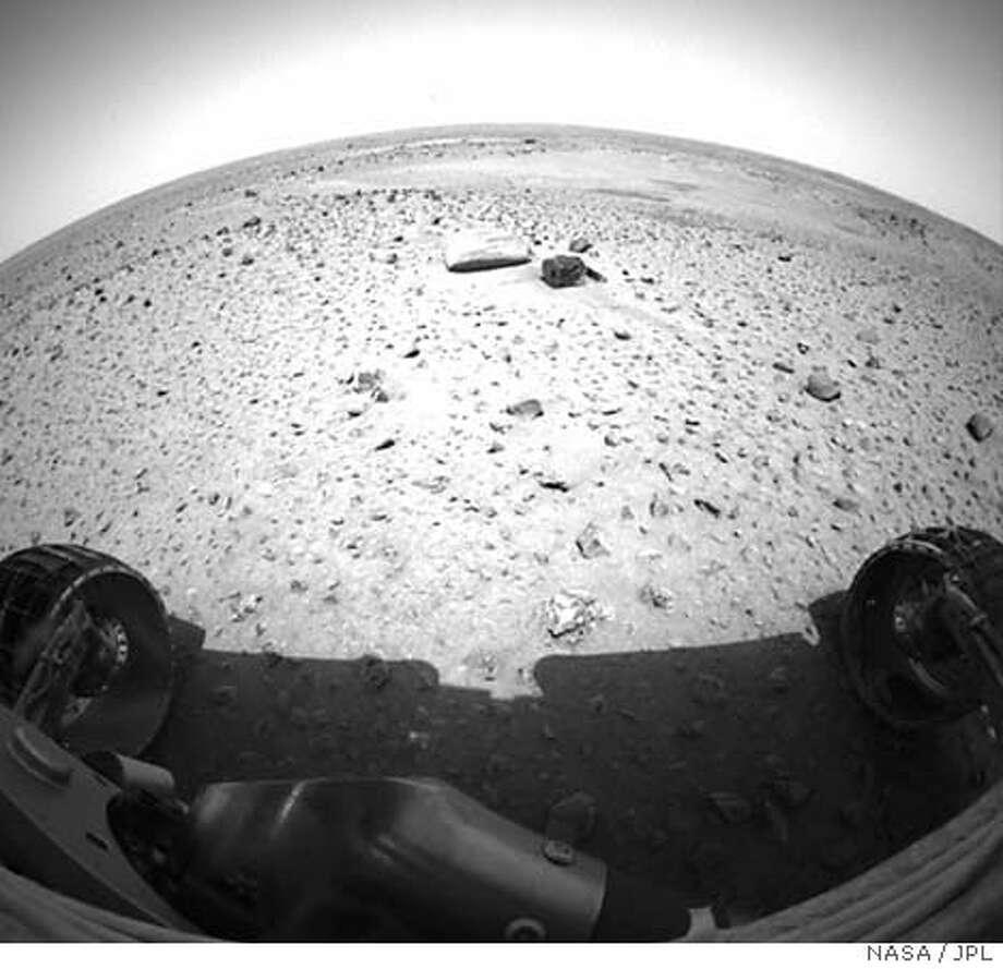 An image from one of the Mars Exploration Rover Spirit's cameras shows the rover's view of the Martian landscape from its new position 1 meter (3 feet) northwest of the lander, after NASA scientists sent the robotic rover out for its first spin on Martian soil, early January 15, 2004. Mission controllers at the Pasadena-based Jet Propulsion Laboratory beamed instructions to roll the six-wheeled vehicle off its landing platform 12 days after it arrived on the red planet. EDITORIAL USE ONLY B&W ONLY AVAILABLE. REUTERS/NASA/JPL Photo: NASA