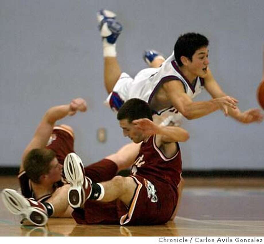St. Ignatius's Max Mizono, goes diving for a loose ball over Northgate's Ricky Feher, rear, and Ryan Kielhorn in the third quarter of the SI Wildcats' victory over the Northgate Broncos at SI in San Francisco, Ca., on Tuesday, March 9, 2004. Photo taken on 03/09/04, in San Francisco, Ca. Photo by Carlos Avila Gonzalez/The San Francisco Chronicle Photo: Carlos Avila Gonzalez