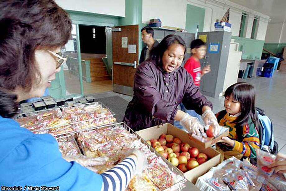 Lunch bunch: Parent Josephine Evardo Echon, right, helps employee Hai Ling serve lunch at Francis Scott Key's summer school session. Chronicle photo by Chris Stewart