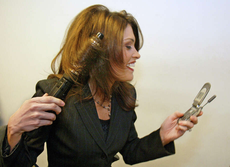 Co-anchor Kimberly Guilfoyle Newsom does her hair while listening to her voicemail after filming the Court TV program Both Sides in New York City, Wednesday, Feb 4, 2004. (AP Photo/Stuart Ramson) Photo: STUART RAMSON