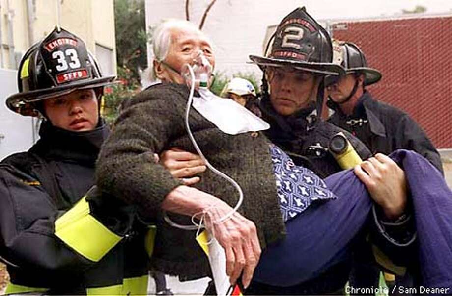 SENIORS FIRE 1/C/14AUG97/MN/SD - Clementina Towers resident Ms. Yee, 98-years-old, is carried to safety by San Francisco firefighter Patricia Yeun, left, and firefighter Caroline Paul, right, at a three alarm fire at Clementina Towers in San Francisco Thursday. (CHRONIcle PHOTO BY SAM DEANER) Photo: SAM DEANER
