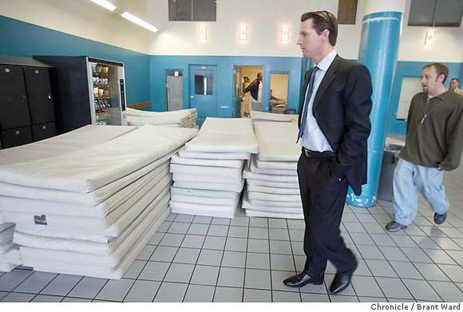 homeless001_bw.jpg Mayor Gavin Newsom made a surprise inspection of two San Francisco homeless shelters Thursday. Here at MSC South located at Fifth and Bryant Streets he toured the biggest city shelter. Here he takes a look at the mattresses stacked on the bottom floor with social services manager Nathan Lawson. BRANT WARD / The Chronicle MANDATORY CREDIT FOR PHOTOG AND SF CHRONICLE/ -MAGS OUT Photo: BRANT WARD