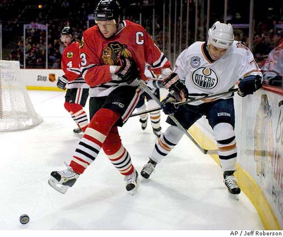 Chicago Blackhawks' Alex Zhamnov, front left, of Russia uses his skate to clear the puck from behind the Blackhawks' goal as he gets tangled up with Edmonton Oilers' Adam Oates, right, and the Blackhawks' Bryan Berard (4) looks on during the first period Sunday, Jan. 4, 2004 in Chicago. (AP Photo/Jeff Roberson) Photo: JEFF ROBERSON