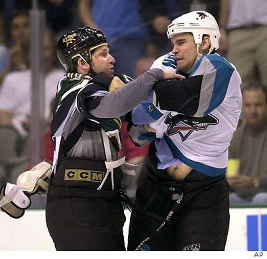 San Jose Sharks Rob Davison, right, and Dallas Stars Shayne Corson fight in the first period in Dallas, Sunday, March 7, 2004. (AP Photo)