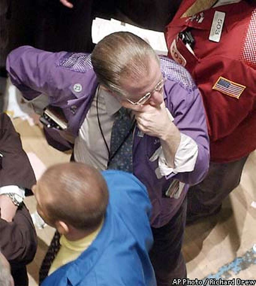 Broker Bernard Schumer, center, pauses a moment as he works on the trading floor of the New York Stock Exchange, Friday June 7, 2002. Reduced outlooks from chip manufacturer Intel and drug maker Biogen sent technology stocks sharply lower Friday in a selloff that spread across the market. (AP Photo/Richard Drew) Photo: RICHARD DREW