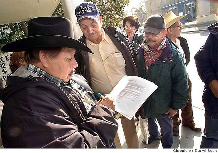 Bracero, Cecilio Santillana, 76, of San Jose, left, and several other braceros and surviving family members sign a letter provided by organizer Jose Sandoval outside the Mexican consulate in San Jose. The letter to Mexican president, Vicente Fox, is requesting payment for the bracero program which decucted 10 percent of the workers' pay in the US and was supposed to be held for them in Mexico. 1/13/04 in San Jose. DARRYL BUSH / The Chronicle Photo: DARRYL BUSH