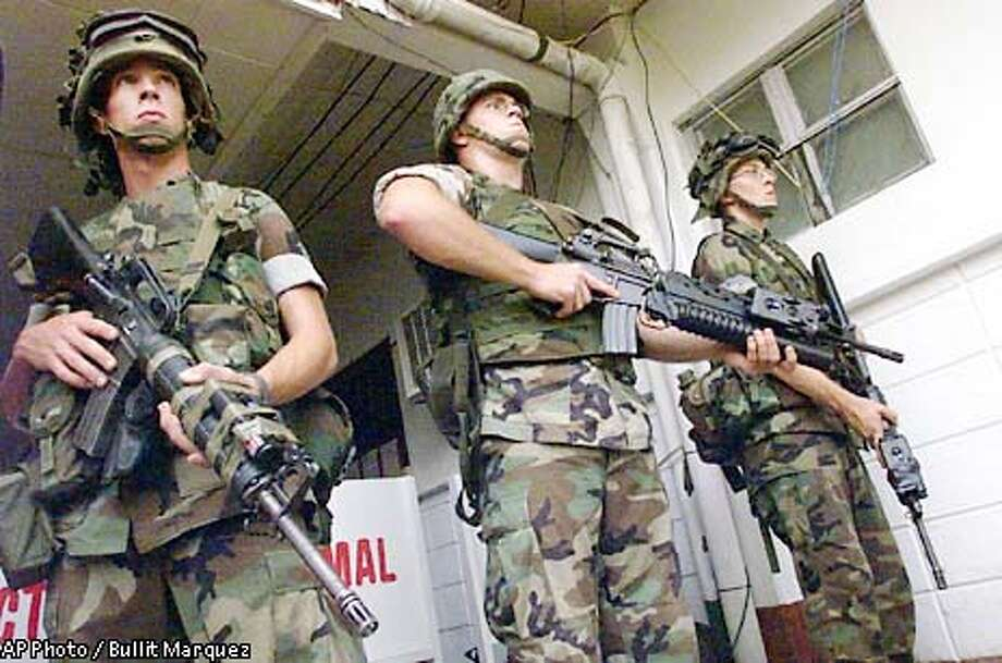 U.S. troopers guard the military hospital in Zamboanga city in southern Philippines where freed American hostage Gracia Burnham is being treated for the gunshot wound she sustained in the rescue operation Friday, June 7, 2002. Authorities confirmed that Martin Burnham, the husband of Gracia, was killed in the firefight along with at least four members of the Muslim Abu Sayyaf kidnappers. (AP Photo/Bullit Marquez) Photo: BULLIT MARQUEZ